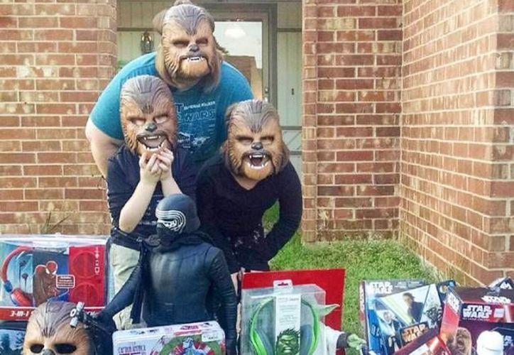 Candace Payne posa en el jardin de su casa junto a sus dos hijos y la máscara del personaje de 'Star Wars' que ha contribuido a popularizarla en todo el mundo. (Facebook de Candace Payne)