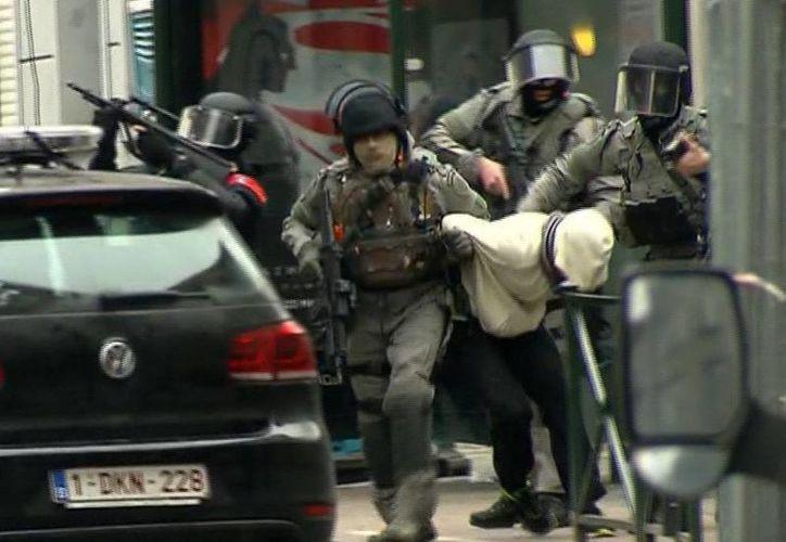 Policías escoltan a Salah Abdeslam tras su arresto en  Molenbeek, Bruselas por su probable participación en los atentados terroristas de París, donde murieron 130 personas, el 13 de noviembre del año pasado.  (AP)