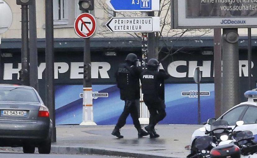 Un par de policías camina frente al mercado de comida kosher donde un hombre armado tiene como rehenes a varias personas. (Agencias)