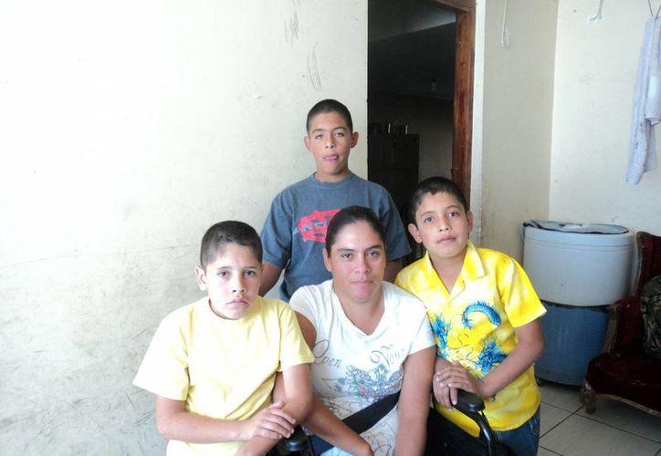 Siri Alatorre, ahora en silla de ruedas a causa de la violencia familiar que sufrió, con sus tres hijos. (Notimex)
