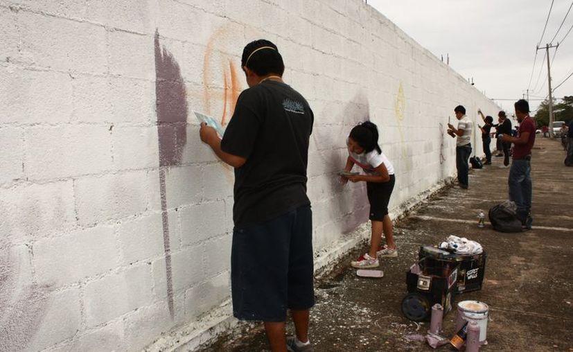 Jóvenes plasman su visión sobre la vida y la muerte en la barda norte del Cementerio de Xoclán. (SIPSE)