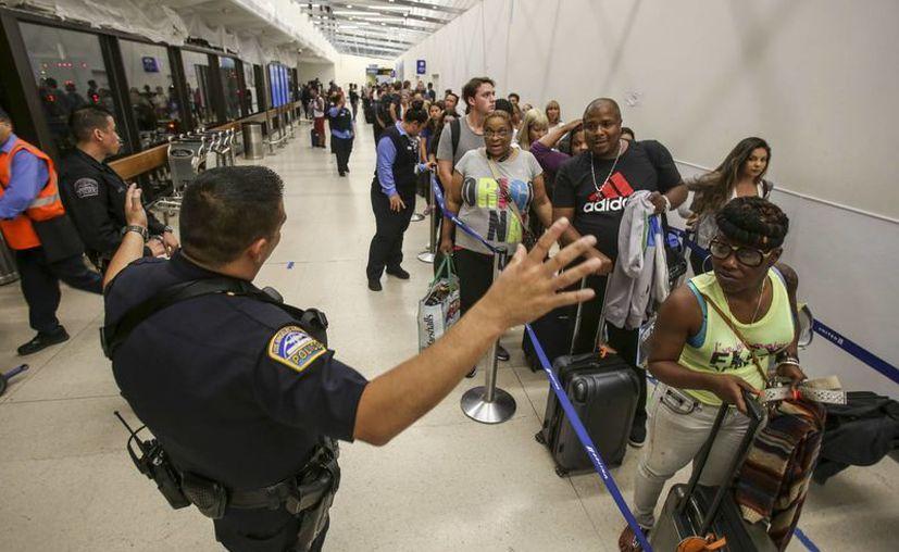 Los oficiales de policía hacen guardia ya que los pasajeros esperan en fila en la Terminal 7 en el aeropuerto internacional de Los Ángeles. (AP/Ringo H. W. Chiu)