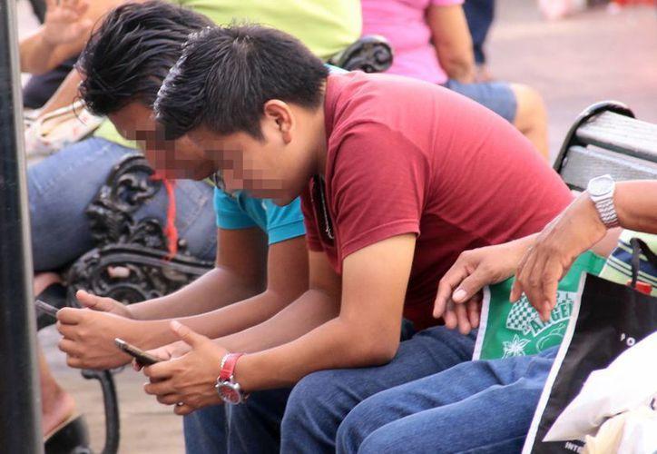 Dos jóvenes revisan su celular en un lugar público. Se recomienda  no subir cosas a la red social de las que te puedes arrepentir. (Milenio Novedades)