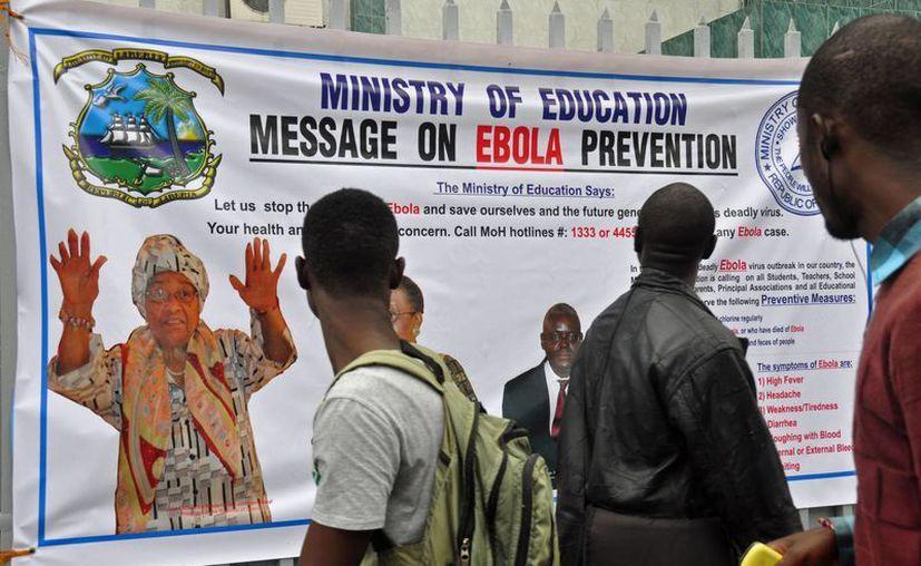 Jóvenes leen un cartel en Monrovia, Liberia, donde la presidenta Ellen Johnson qué hacer ante un caso de ébola. (AP)