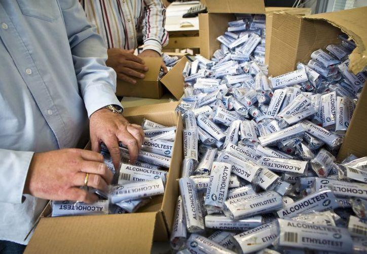 Dos empleados empaquetan test alcoholímetros en la sede de una asociación automovilística de Bunnik, Holanda. (EFE/Archivo)