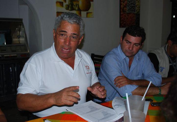 Miguel Ángel Lemmus Mateos (izquierda) habla sobre la reactivación de dos de las cuatro torres de 20 niveles en el desarrollo conocido como Puerto Cancún. (Tomás Álvarez/SIPSE)