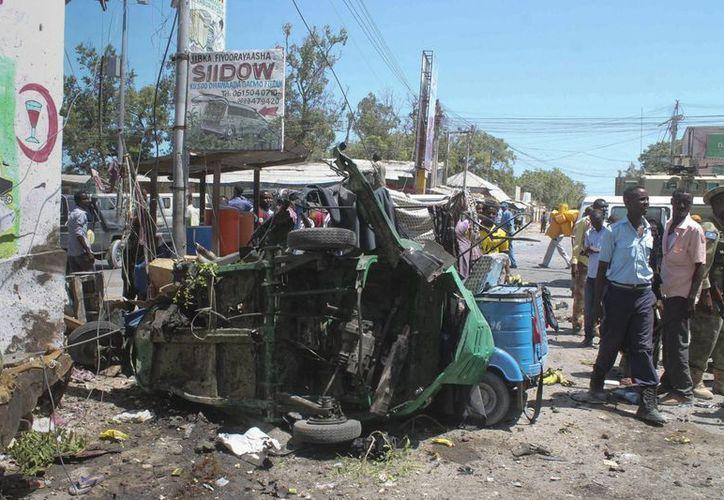 Miembros de las Fuerzas de Seguridad somalíes pasan junto a los restos de un vehículo delante de un edificio gubernamental atacado por yihadistas en Mogdiscio, Somalia el pasado 14 de abril. (EFE)