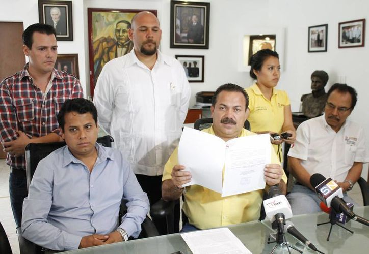 El presidente municipal de Benito Juárez, Julián Ricalde Magaña (centro), muestra la solicitud de construcción del Dragon Mart. (Jesús Tijerina/SIPSE)