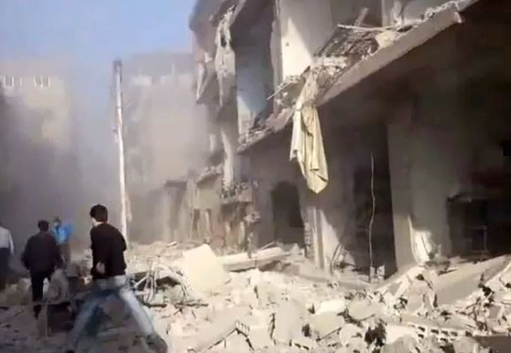 Un hombre sirio corre a auxiliar a personas heridas tras un bombardeo en Damasco. (Agencias)