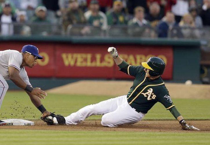 El tercer base de Rangers de Texas,  Adrian Beltre (i) trata de ponchar a Jed Lowrie de Atléticos de Oakland en el tercer inning. (Foto: AP)