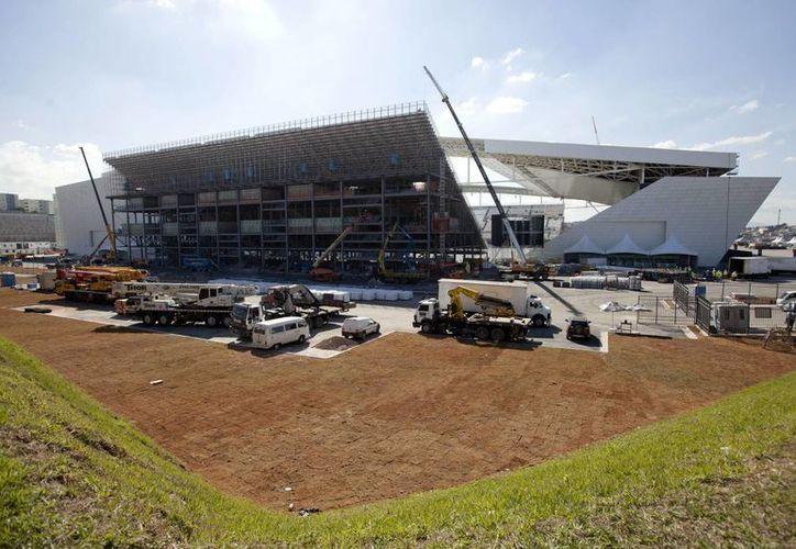 Obreros trabajan en las afueras del estadio Arena Corinthians, sede de la apertura del Mundial de Fútbol Brasil 2014, el lunes 12 de mayo. (EFE)