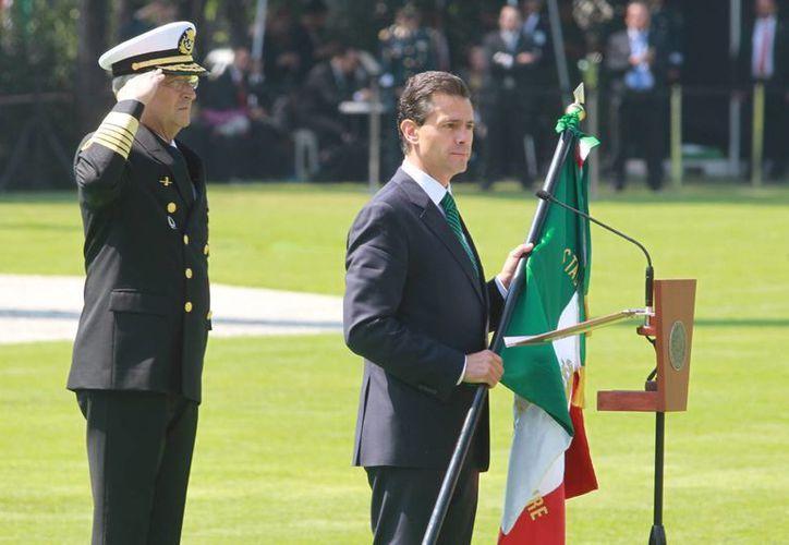 Imagen del presidente Enrique Peña Nieto, durante la ceremonia de Protesta de Bandera de los Soldados del Servicio Militar Nacional Clase 1996, anticipados, remisos y mujeres voluntarias, en el Campo Marte de la ciudad de México. (Notimex)