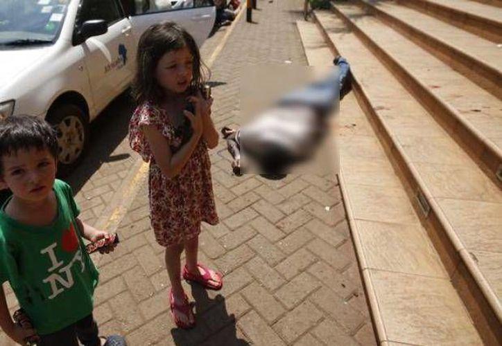 Elliott y su hermana Amelie, claramente consternados, fueron luego fotografiados fuera del centro comercial, con el chocolate, y un cadáver tras de ellos. (Reuters)