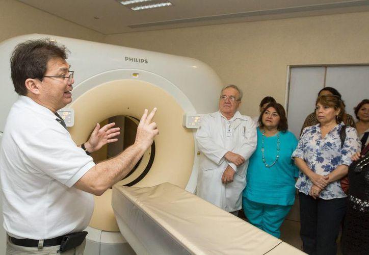 El titular de la SSY, Jorge Mendoza (i) explica cómo a través del Tomógrafo Multicorte detectan lesiones en las pacientes. (Cortesía)
