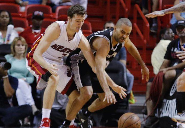 Tony Parker (c) disputa un balón contra Goran Dragic (7), en partido en que Spurs ganó a Heat, al igual que en la final del año pasado en la NBA. (Foto: AP)