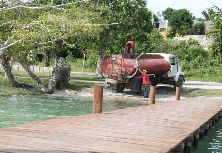 Con una pipa, la empresa Arcadio Valle extrae el agua que, dicen, no perjudica a la laguna, asegura Eduardo Tadeo Esteban, director de Servicios Públicos Municipales y Desarrollo Urbano. (Juan Carlos Gómez/SIPSE)