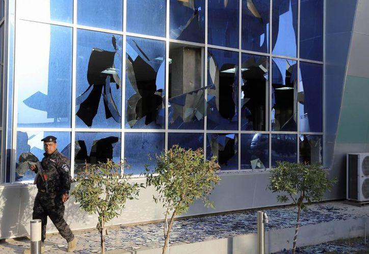 Un policía federal iraquí camina frente a las instalaciones del Ministerio de Transporte donde esta mañana se produjo un asalto con saldo de ocho muertos. (Agencias)