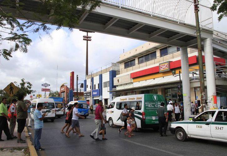 Las personas prefieren arriesgar su vida al cruzar la avenida Tulum de Cancún, antes de usar el puente peatonal. (Yajahira Valtierra/SIPSE)