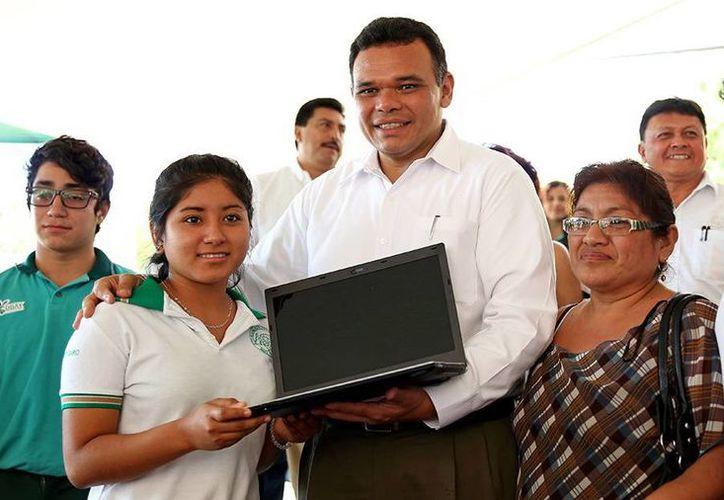 El gobernador Rolando Zapata Bello entrega una computadora a una alumna del Conalep, ayer viernes. (SIPSE)