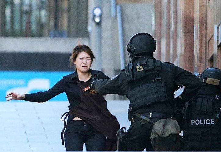 Una rehén corre hacia un policía, luego de huir de la cafetería donde estaba secuestrada. (Agencias)