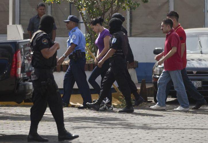 Escoltados por la policía nicaraguense, los presuntos reporteros de Televisa son llevados ante el juez de la causa. (Agencias)