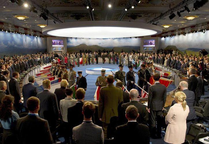 Militares de países de la OTAN que ha sufrido bajas portan banderas de sus países antes de guardar un minuto de silencio por los fallecidos en Afganistán, al comienzo de la cumbre bianual que se celebró el 4 y 5 de septiembre, en Newport, Gales, Reino Unido. (EFE/Archivo)