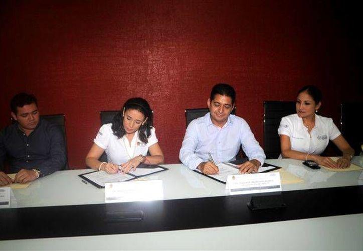 El delegado del Issste en Q. Roo, segundo de izquierda a derecha, Carlos Hernández Blanco, en la firma de un convenio con el IQM. (Harold Alcocer/SIPSE)