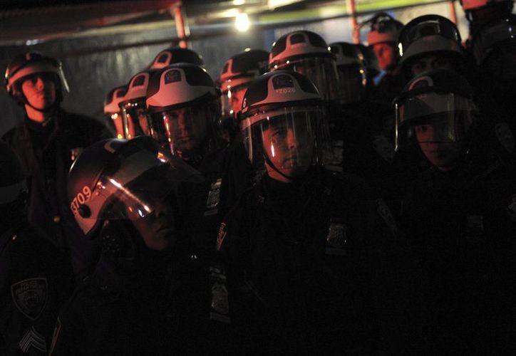 Policías antidisturbios permanecen alerta en una calle de Nueva York. (EFE)