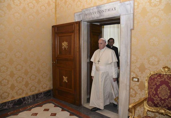 El Papa llega a un salón del Vaticano para una reunión privada con el presidente de Austria (fuera de foco), el 13 de noviembre de 2014. (AP)