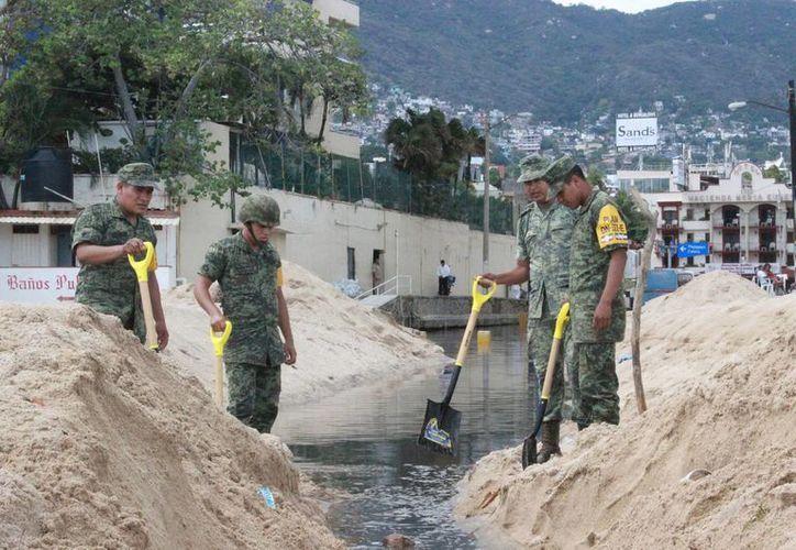 Elementos del Ejército Mexicano aplicaron el Plan DN-III para auxiliar en el desazolve de toneladas de arena que sacó el alto oleaje en Acapulco a consecuencia de la tormenta tropical Carlos. (Notimex)
