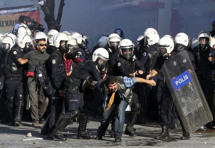 Policías antimotines detienen a manifestantes tiempo durante una protestaba contra las políticas de Turquía en Siria, en Ankara, Turquía, el martes 7 de octubre de 2014. (Foto: AP/Burhan Ozbilici)