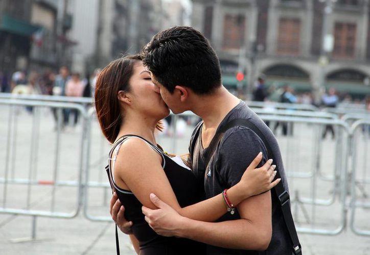Especialistas del IMSS recomiendan mantener una buena higiene bucal para evitar enfermedades que se transmiten por el beso. Imagen de contexto de una pareja besándose, en la Ciudad de México. (Archivo/Notimex)