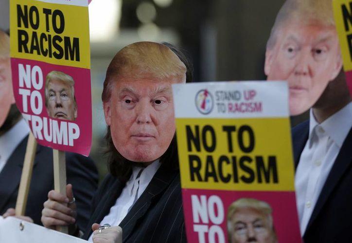 En EU y otras partes del mundo se han realizado protestas en contra de Donald Trump. Manifestación contra el magnate afuera de la embajada de EU en Londres. (AP/Alastair Grant)