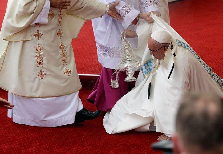 Sacerdotes ayuda al Papa Francisco a levantarse, luego de que cayera en pleno altar, durante una misa en Polonia. (AP)