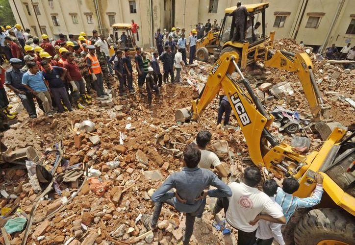 Equipos de rescate trabajan en las labores de búsqueda en los dos edificios que se derrumbó en Baroda, India. (EFE)