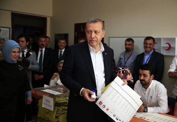 El ministro turco Recep Tayyip Erdogan, acompañado por su esposa, se dispone a votar. (Foto:AP)
