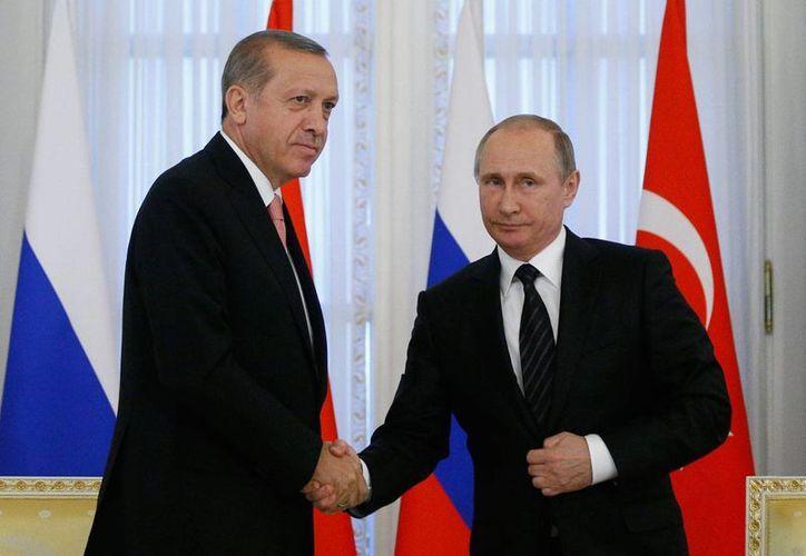 El presidente turco Recep Tayip Erdogan y su homólogo ruso Vladímir Putin se estrechan las manos al inicio de la cumbre bilateral que se celebra en San Petersburgo, Rusia. (AP Photo/Alexander Zemlianichenko)