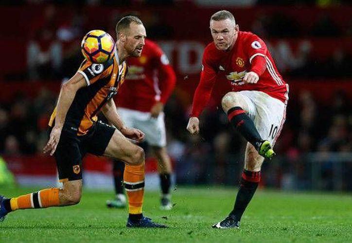 Wayne Rooney dispara ante la oposición de David Meyler. El Manchester United, que empató 0-0 ante Hull, se aleja cada vez más del liderato que está en posesión del Chelsea. (marca.com)