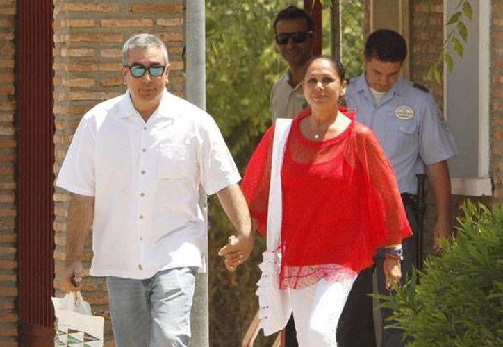 Isabel Pantoja, muy sonriente y con gesto firme, sale de cárcel, tomada de la mano de su hermano Agustín. (AP)