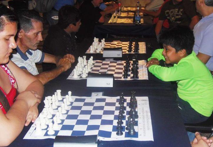Paul Rosales enfrenta a la leyenda viviente del ajedrez, el  Mtro. Alayola en el torneo de la Uady. (Milenio Novedades)