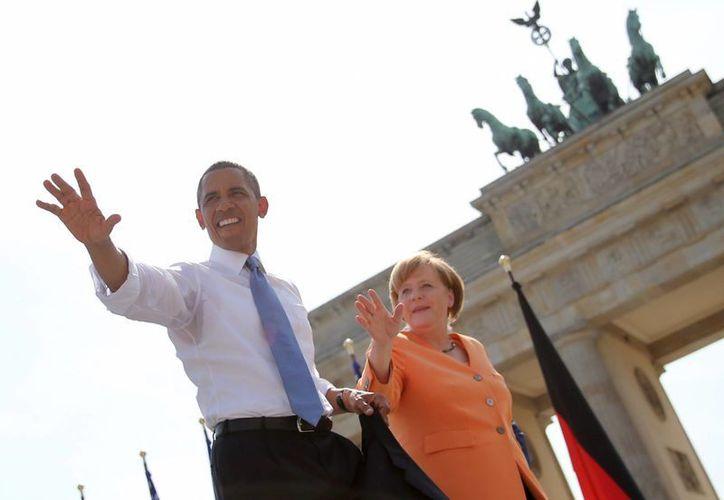 Barack Obama saluda a los invitados junto a la canciller alemana, Angela Merkel, frente a la Puerta de Brandenburgo en la Pariser Platz en Berlín, Alemania, miércoles. (Agencias)