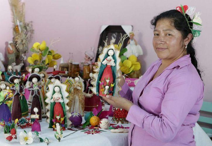 Imagen de la artesana Crescencia García Ramos posando con alguna de las figuras que realiza con la hoja de maíz. (Notimex)