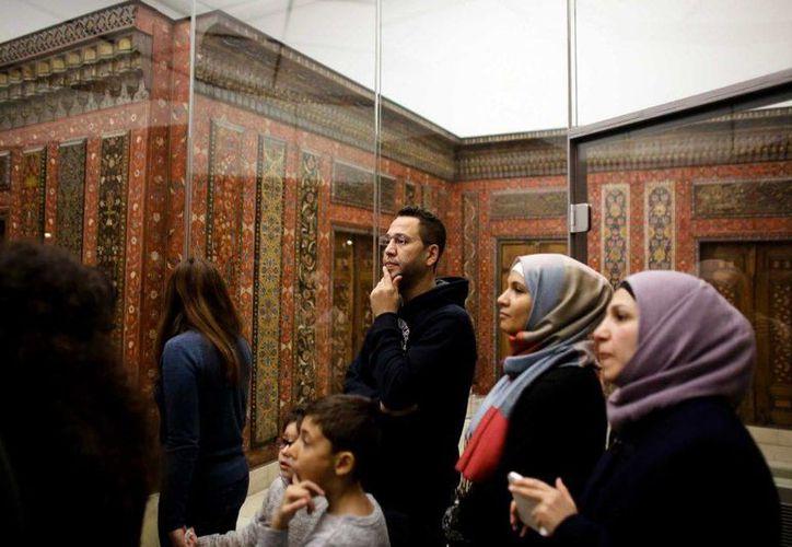 Imagen de un grupo de refugiados que escuchan a un guía en el Museo de Arte Islámico en Berlín. (AP Foto/Markus Schreiber)