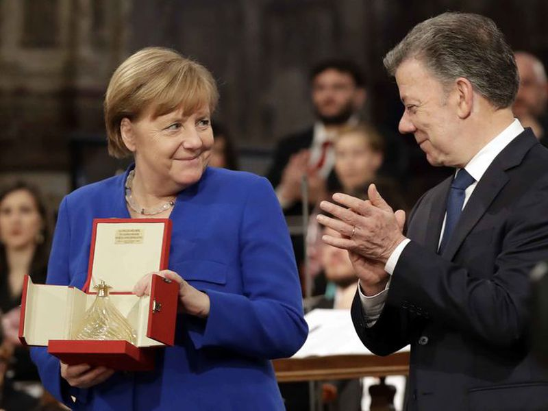 Angela Merkel, flanked by Colombian President, Juan Manuel Santos holds the lamp of peace.