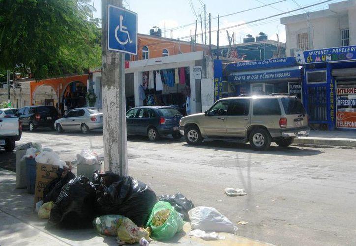Los espacios públicos destinados a personas con discapacidad pocas veces son respetados en Tulum. (Rossy López/SIPSE)