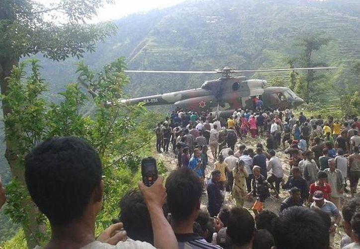 Una multitud observa mientras los equipos de rescate llevan a los heridos de un accidente de autobús a un helicóptero. (Lal Kaji Pahari)