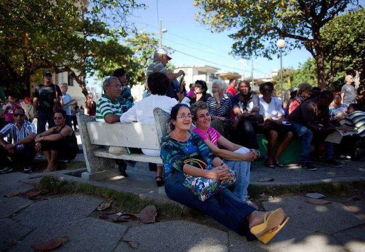 Decenas de ciudadanos esperan ser atendidos en la Oficina de Negocios de EU, en La Habana, para renovar u obtener visas.  (AP Photo/Ramon Espinosa)