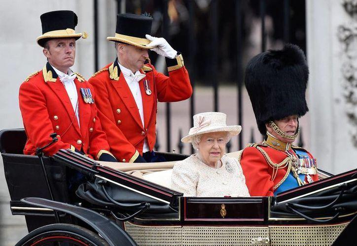 La reina Isabel II junto a su marido el duque de Edimburgo salen hoy del Palacio de Buckingham, durante la celebración del cumpleaños de la soberana. (EFE)