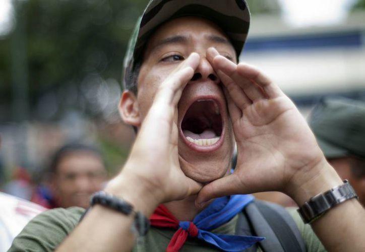 """Un manifestante """"chavista"""", grita consignas a favor del presidente electo Nicolas Maduro marcha frente al Consejo Nacional Electoral, en Caracas, Venezuela. (Agencias)"""
