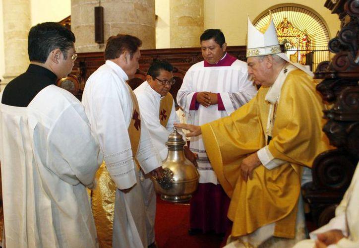 Bendice Monseñor Berlie Belaunzarán uno de los santos óleos. (Christian Ayala/SIPSE)